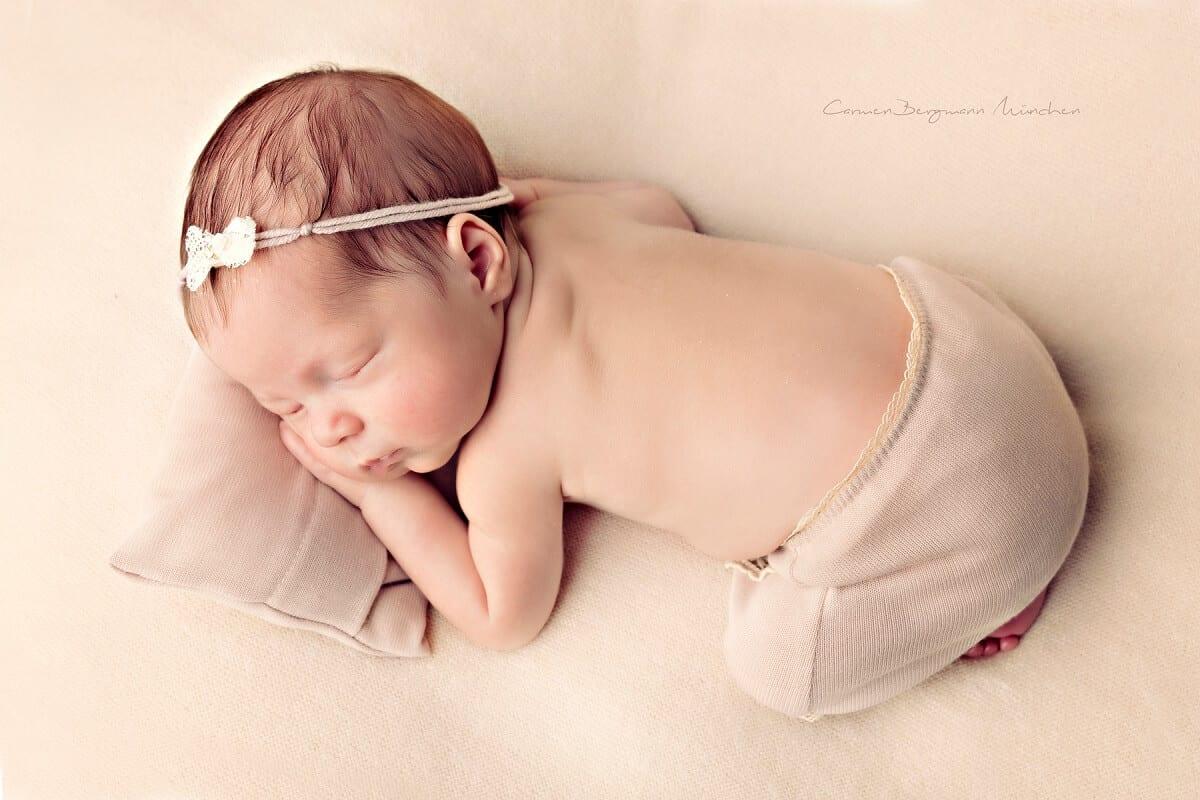 Fotograf fuer Neugeborene in Fotostudio Kleinkind auf Decke suess