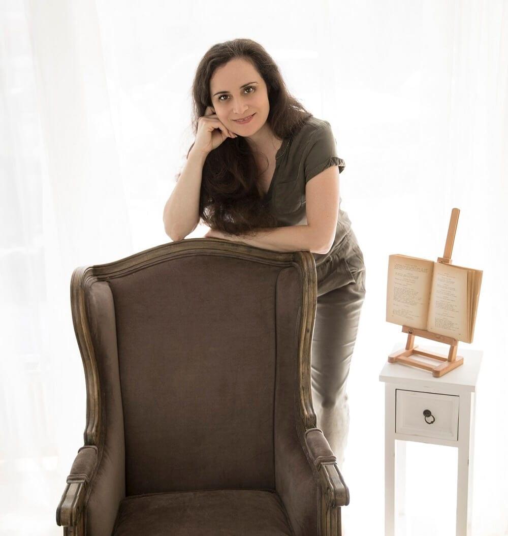 Carmen Bergmann auf einen Stuhl gelehnt in ihrem Fotostudio
