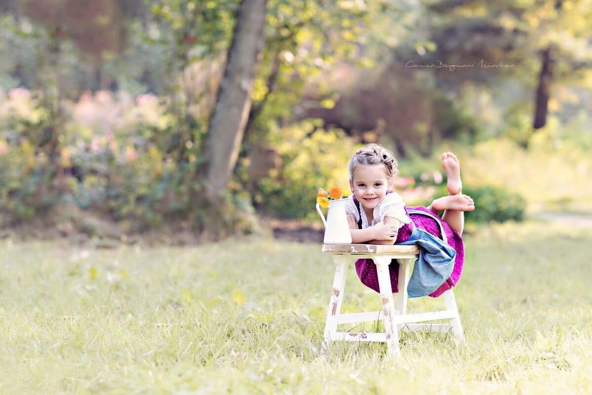 Maedchen auf Bank in Wald Fotoshooting Outdoor fuer Kinder