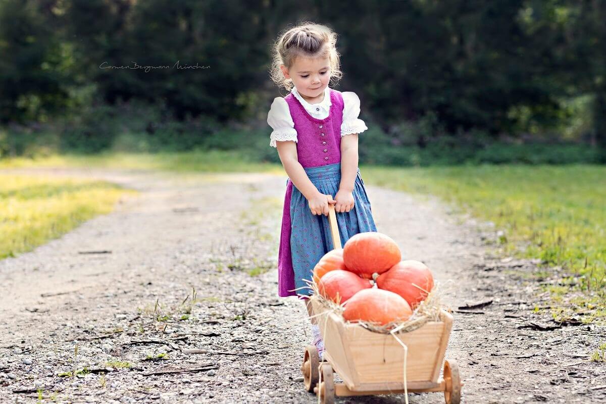 Outdoorkindershooting im Herbst mit Kind und Kuerbis in Wagen im Wald