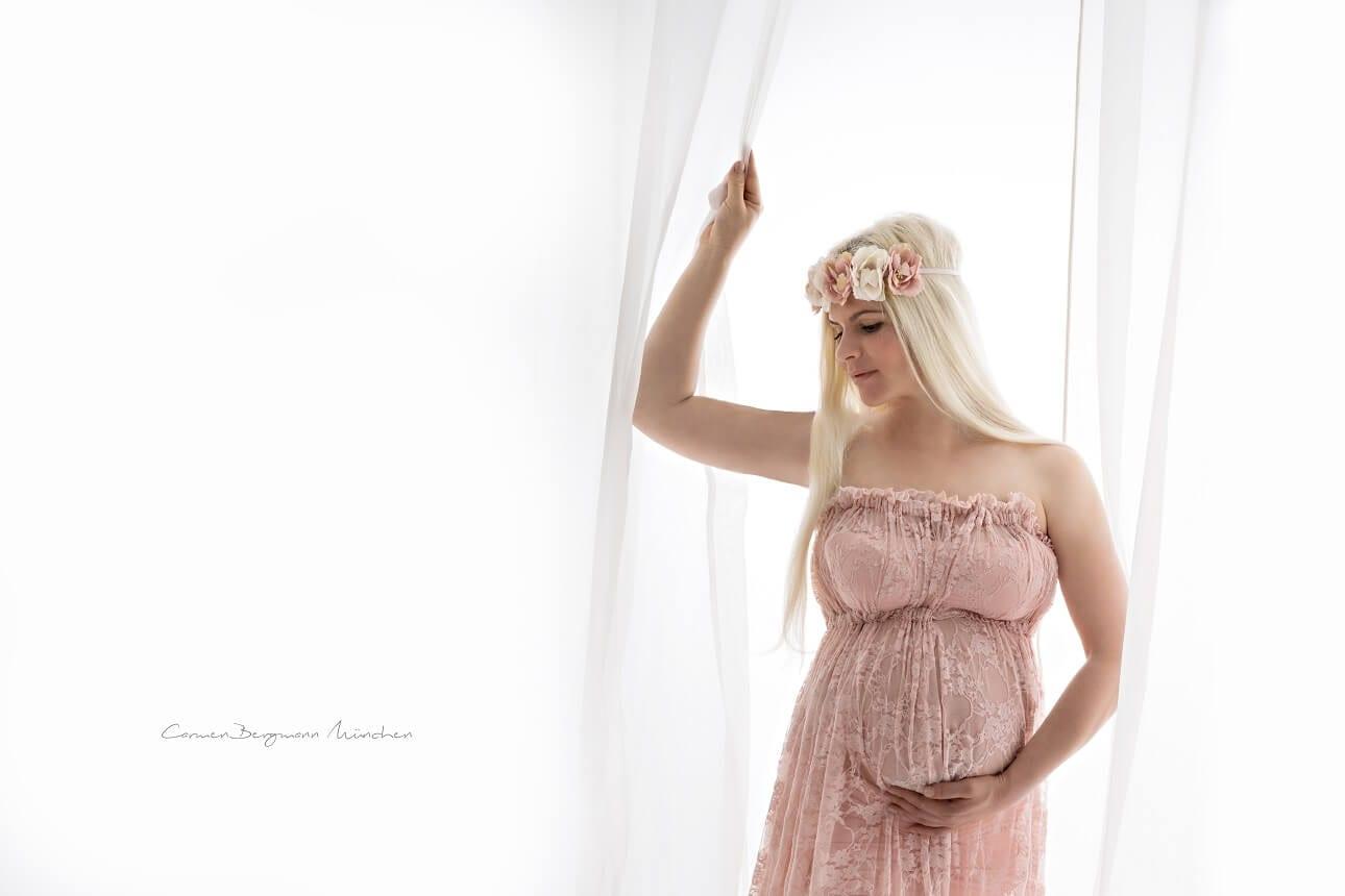 Schwangere Frau mit Babybauch haelt Tuch in Kleid