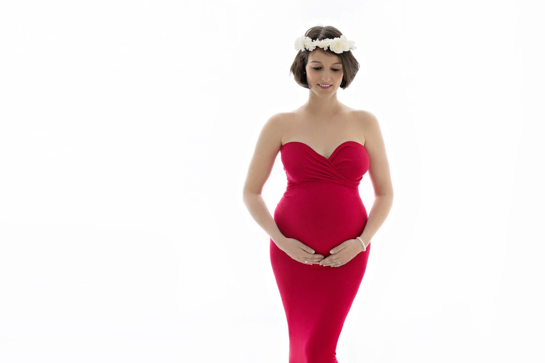 Babybauch-Fotoshooting Frau in rotem Kleid
