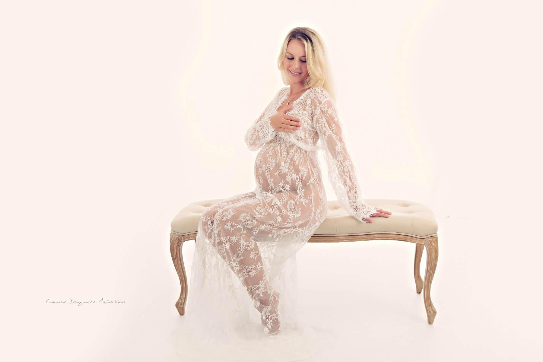 Fotografin Carmen Bergmann Babybauch Shooting blonde schwangere Frau in Fotostudio auf Bank