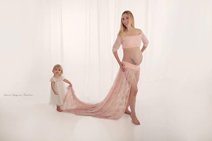 Schwangere blonde Dame im langen rosafarbenen Kleid mit kleiner Tochter im weissen Kleid das das Kleid anhaelt
