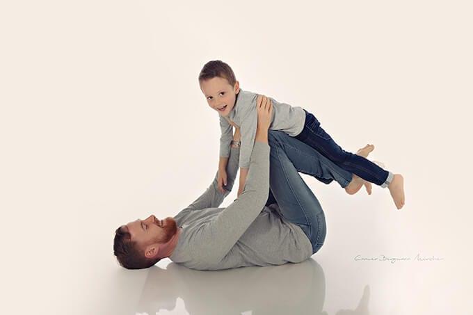 Vater der auf dem Ruecken liegt haelt den jungen Sohn waehrend eines Familienshooting in Carmen Bergmanns Fotostudio in Muenchen hoch ueber dem Boden