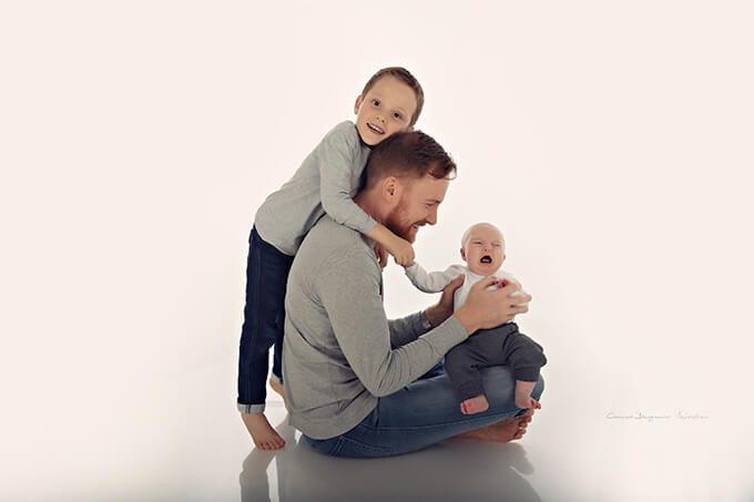 Vater haelt Baby am Knie und Sohn haelt Vater und lachend im Fotostudio Carmen Bergmann waehrend eines gluecklichen Familienschooting in Haidhausen