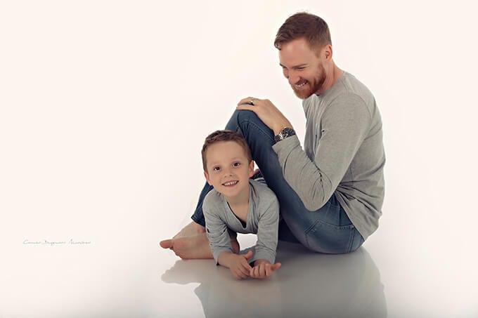 Vater und Sohn gekleidet in graue Blusen sitzen auf dem Boden und laecheln gluecklich im Fotostudio Carmen Bergmann bei einem Familienshooting in Haidhausen