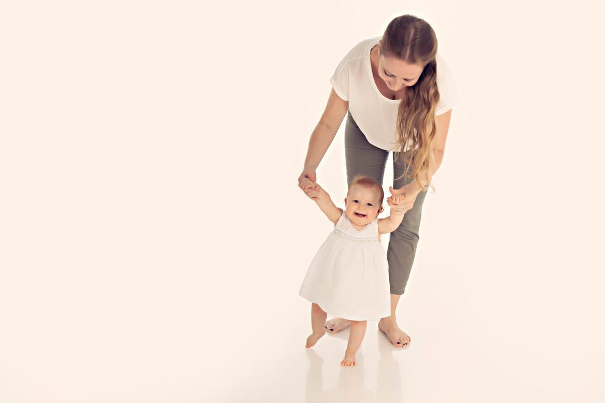 Baby Maedchen laeuft und Mutter haelt ihre Haende waehrend eines Fotoshootings im Studio Carmen Bergmann