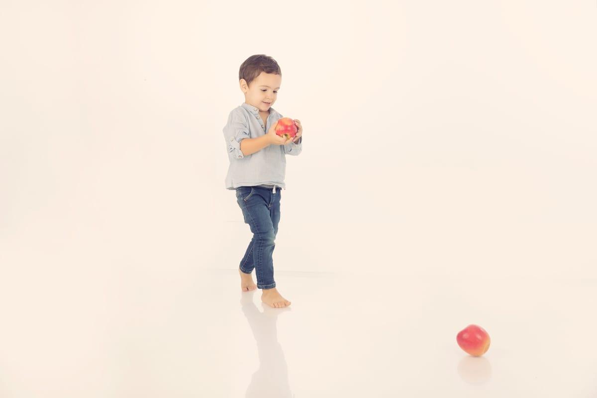 Baby in blauen Outfits spielt mit Obst waehrend eines Baby Fotoshootings im Carmen Bergman Fotostudio in Muenchen