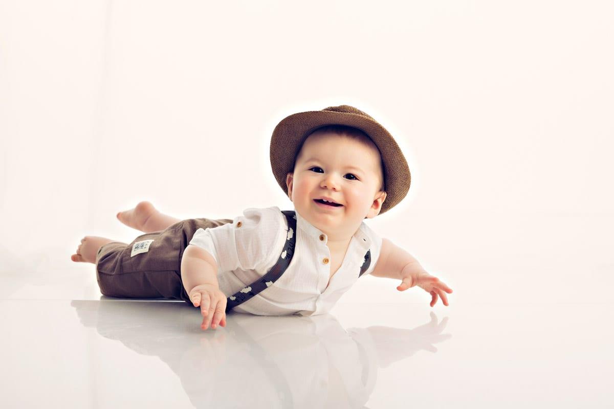 Baby mit einem Hut lag auf seinem Bauch und betrachtet die Kamera in Carmen Bergman Fotostudio