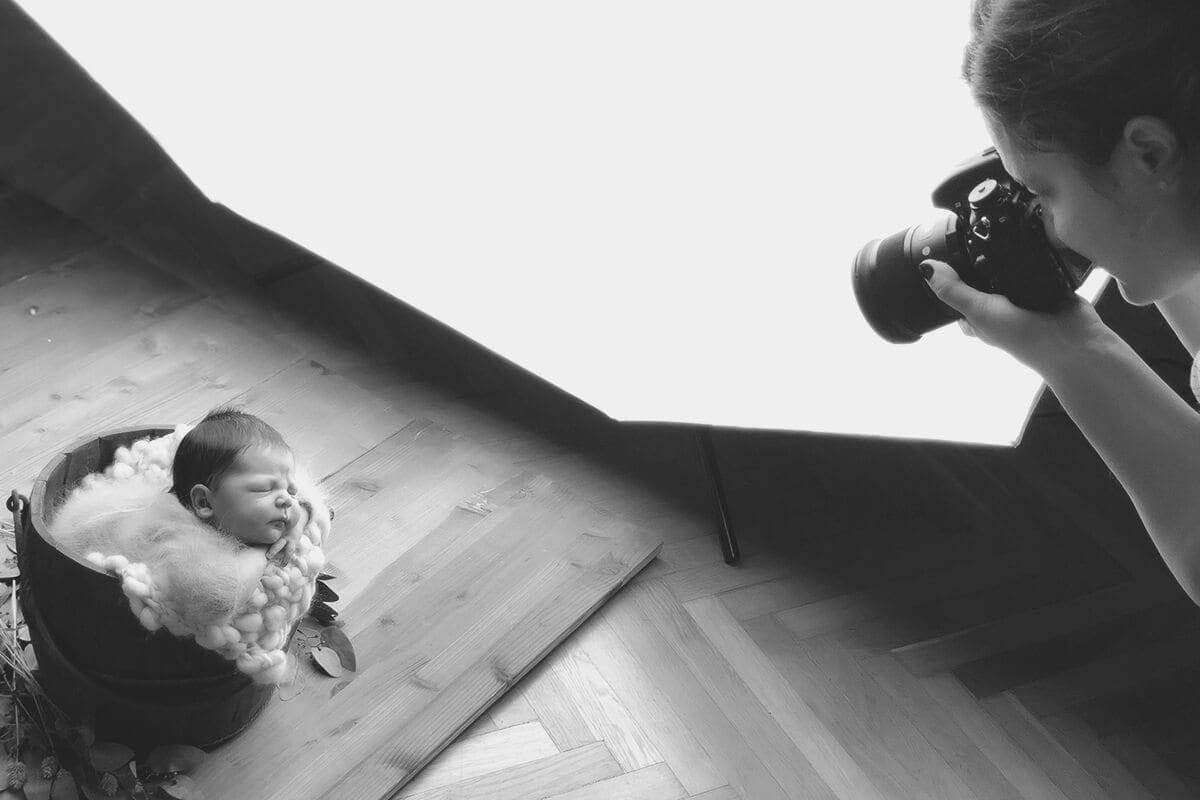 Baby schlaeft ein und Fotograf fotografiert waehrend eines Workshops fuer Neugeborene