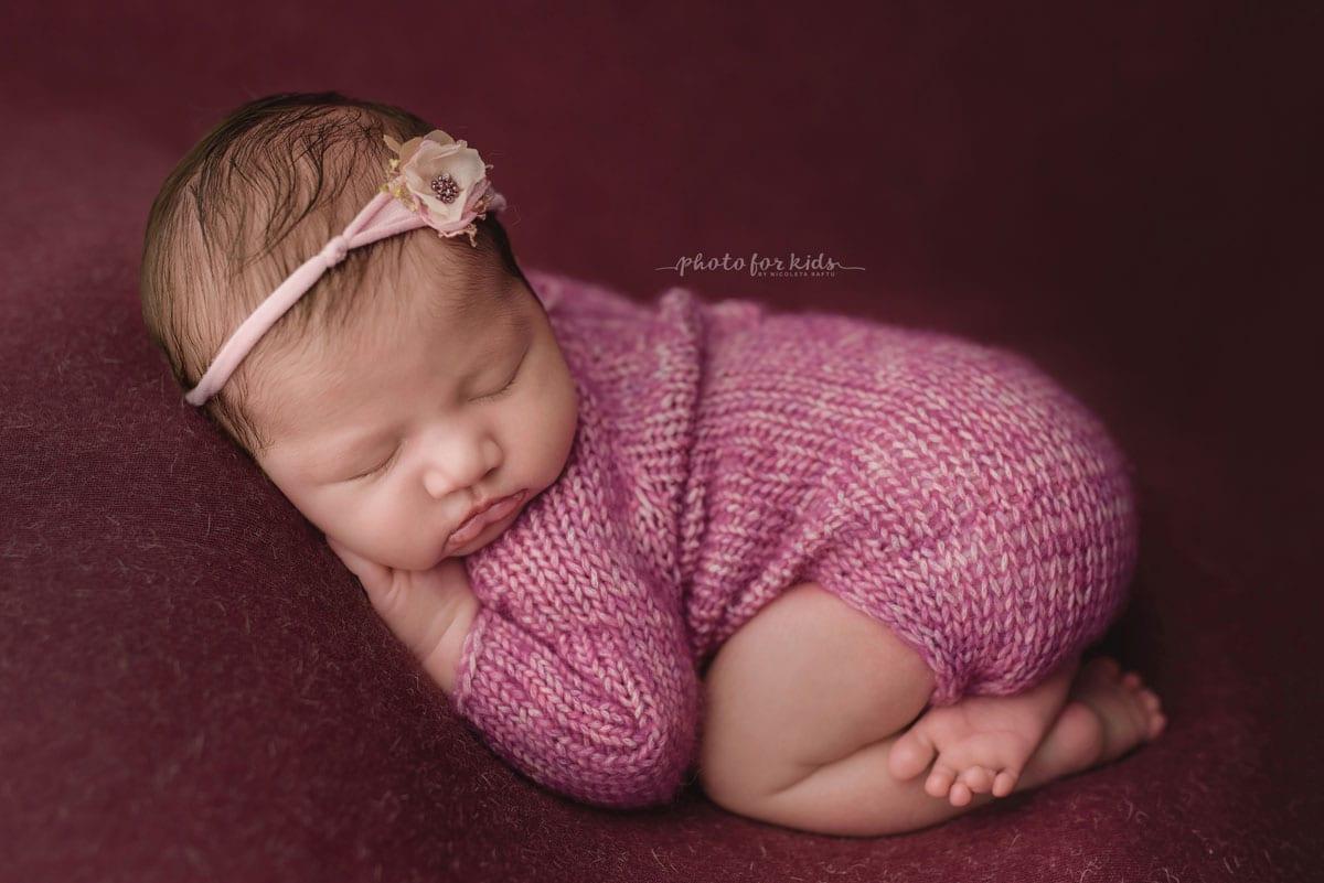Das neugeborene Maedchen in rosafarbenen Outfits schlaeft im neugeborenen Fotoshooting von Nicoleta Raftu