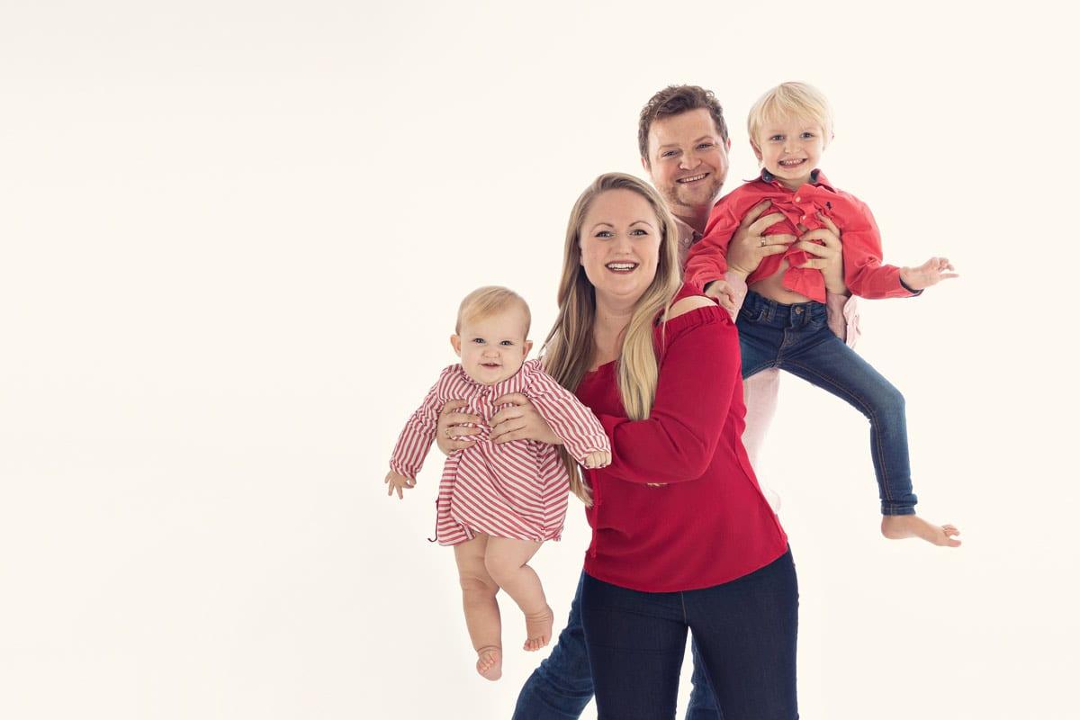 Die Eltern halten ihre beiden Kinder und freuen sich ueber ein Familienfotoshooting im Carmen Bergmann Studio in Muenchen