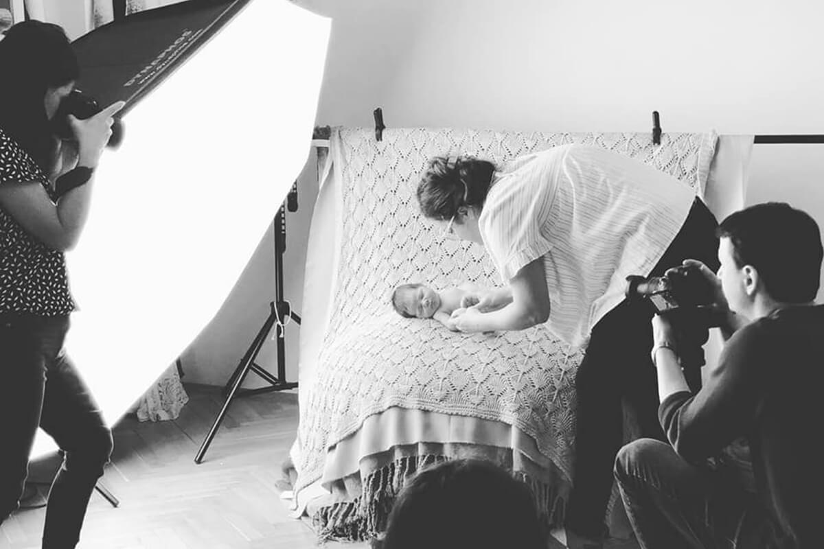 Drei Fotografen fotografieren ein schlafendes Baby waehrend eines Workshops fuer Neugeborene