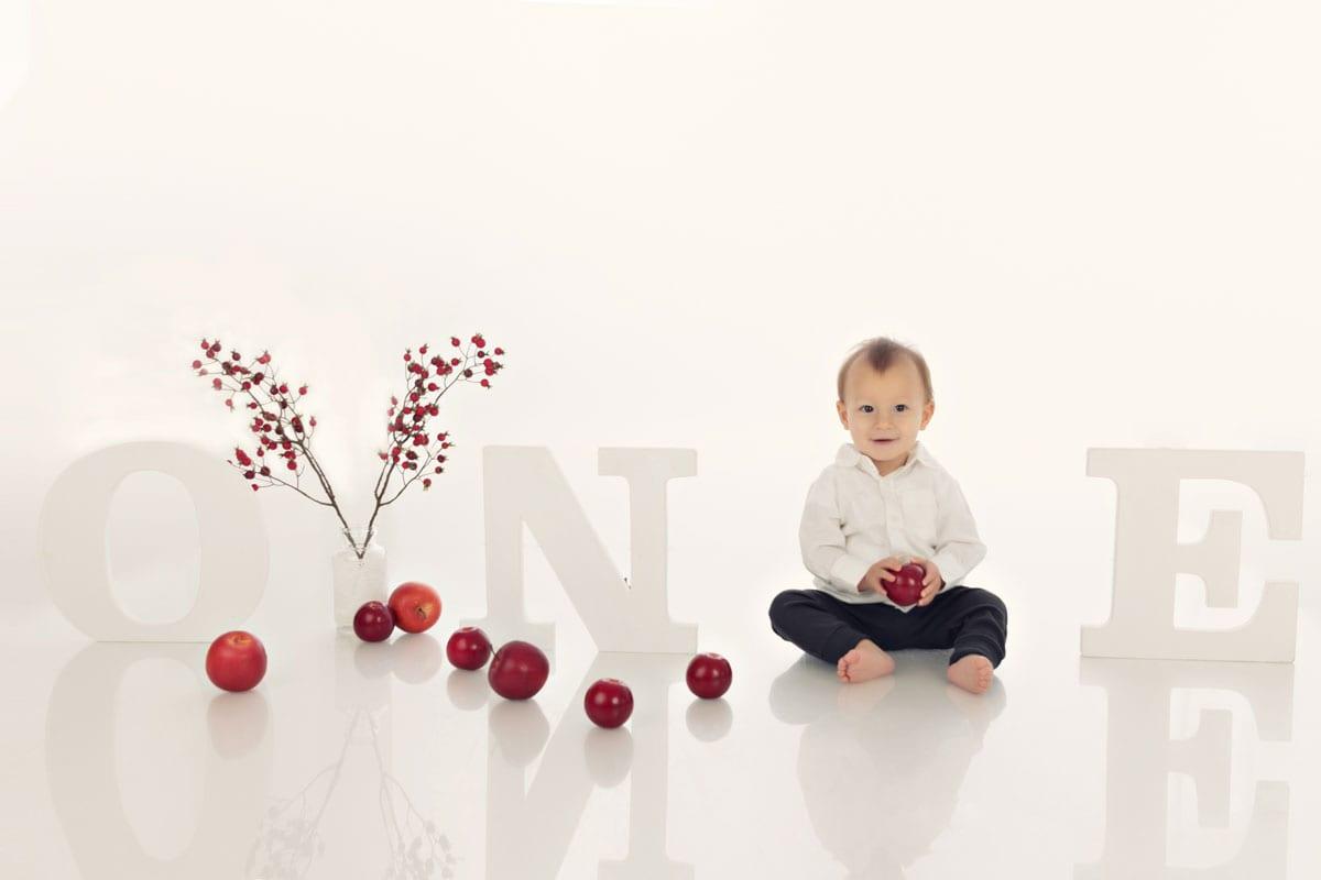 Ein jaehriger Junge sitzt auf dem Boden und spielt mit Aepfeln im Fotostudio von Carmen Bergman waehrend eines Babyfotoshootings