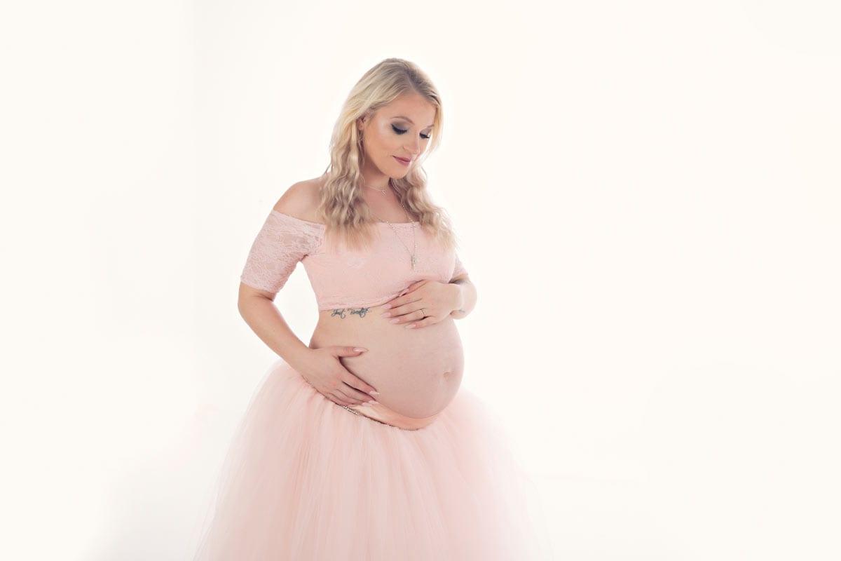 Eine schwangere Frau mit blonden Haaren zeigt ihren Babybauch waehrend eines Babybauch Fotoshootings im Fotostudio von Carmen Bergmann