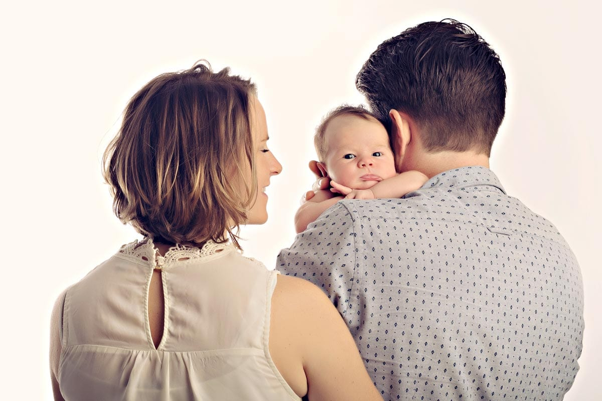 Eltern halten kleinen Jungen der waehrend eines Babyfotoshooting in Carmen Bergman in Muenchen in die Kamera schaut