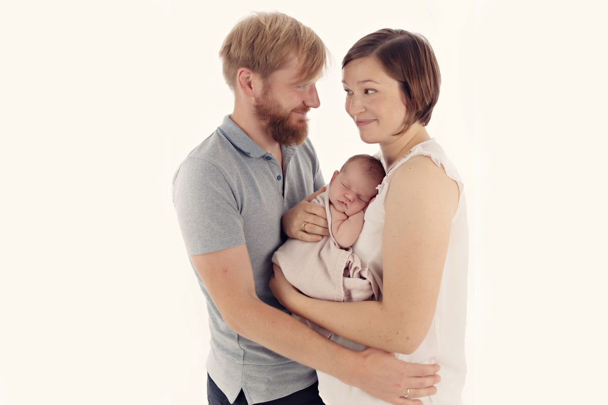 Eltern halten neugeborenes Baby in Armen zwischen ihnen waehrend neugeborenes Fotoshooting in Carmen Bergmann Photo Studio