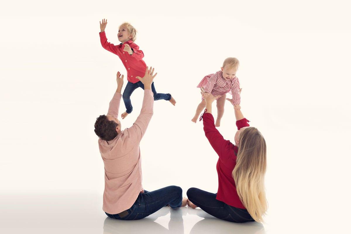 Eltern werfen ihre beiden Kinder in der Luft waehrend eines Fotoshootings im Carmen Bergmann Studio in Muenchen