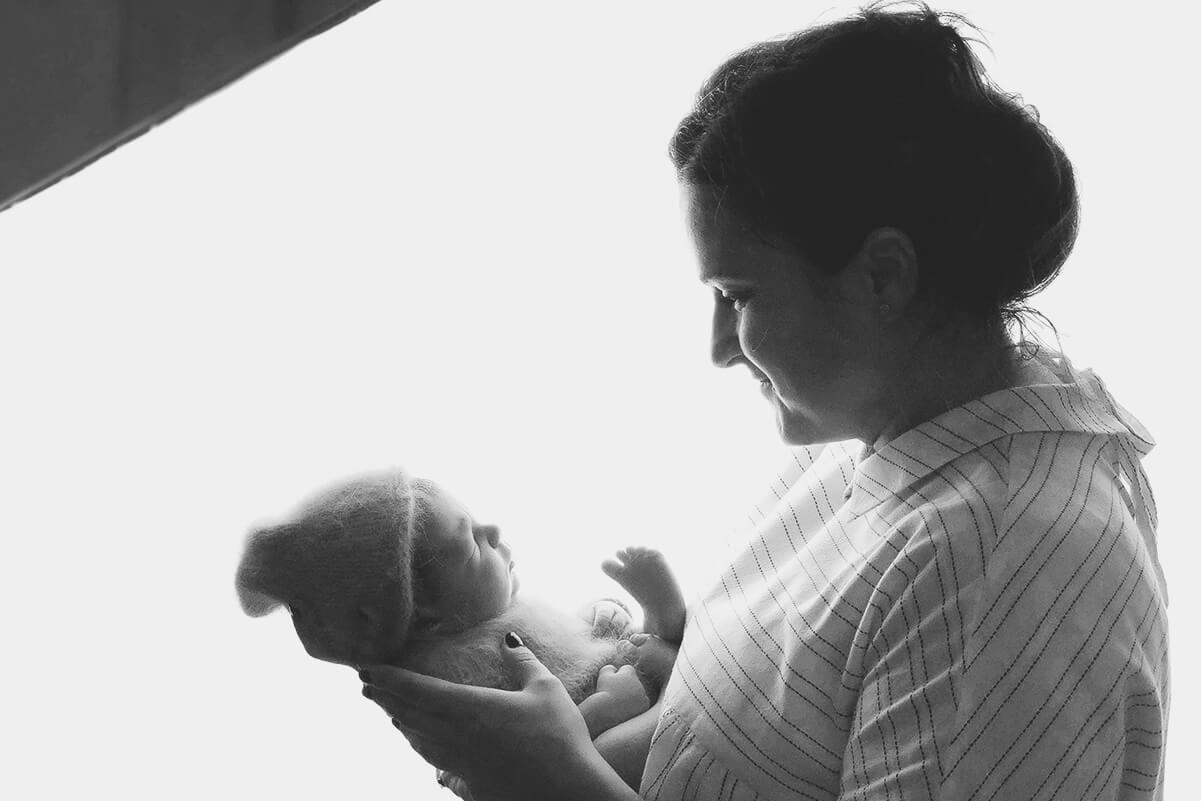 Fotografin die ein Baby fuer ein Fotoshooting waehrend eines neugeborenen Fotografie-Workshops zum Schlafen bringt