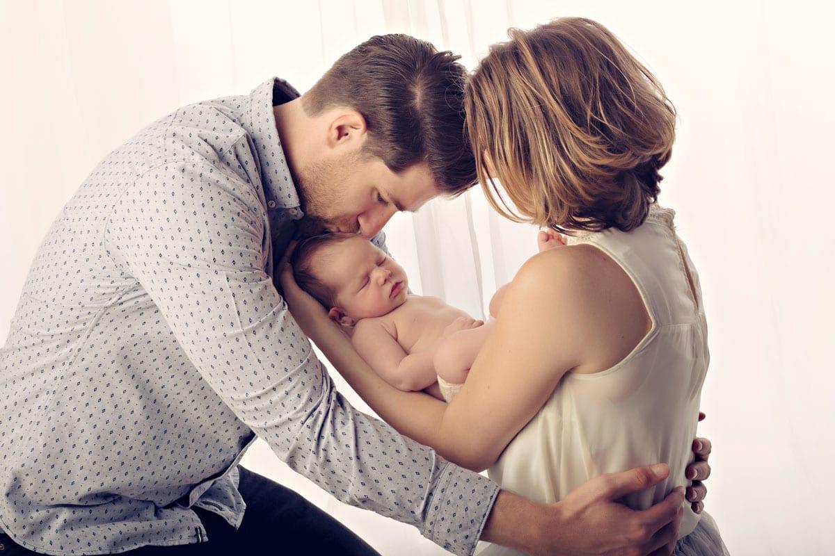 In Carmen Bergmann Fotostudio in Muenchen halten Mutter und Vater ihr Baby und der Vater kuesst sie auf den Kopf