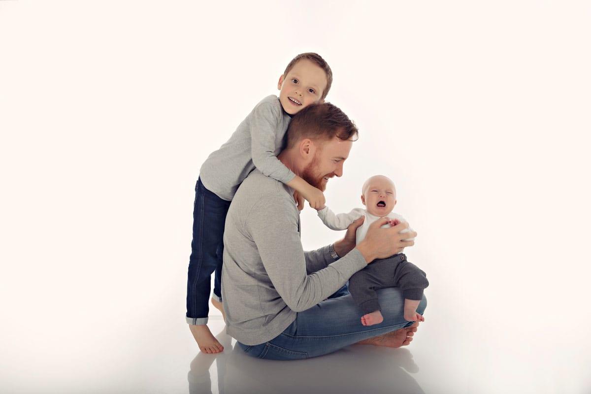 Junge haelt Vater und Vater haelt Baby waehrend eines Familienfotoshooting in Bergmann Photo Studio in Haidhausen