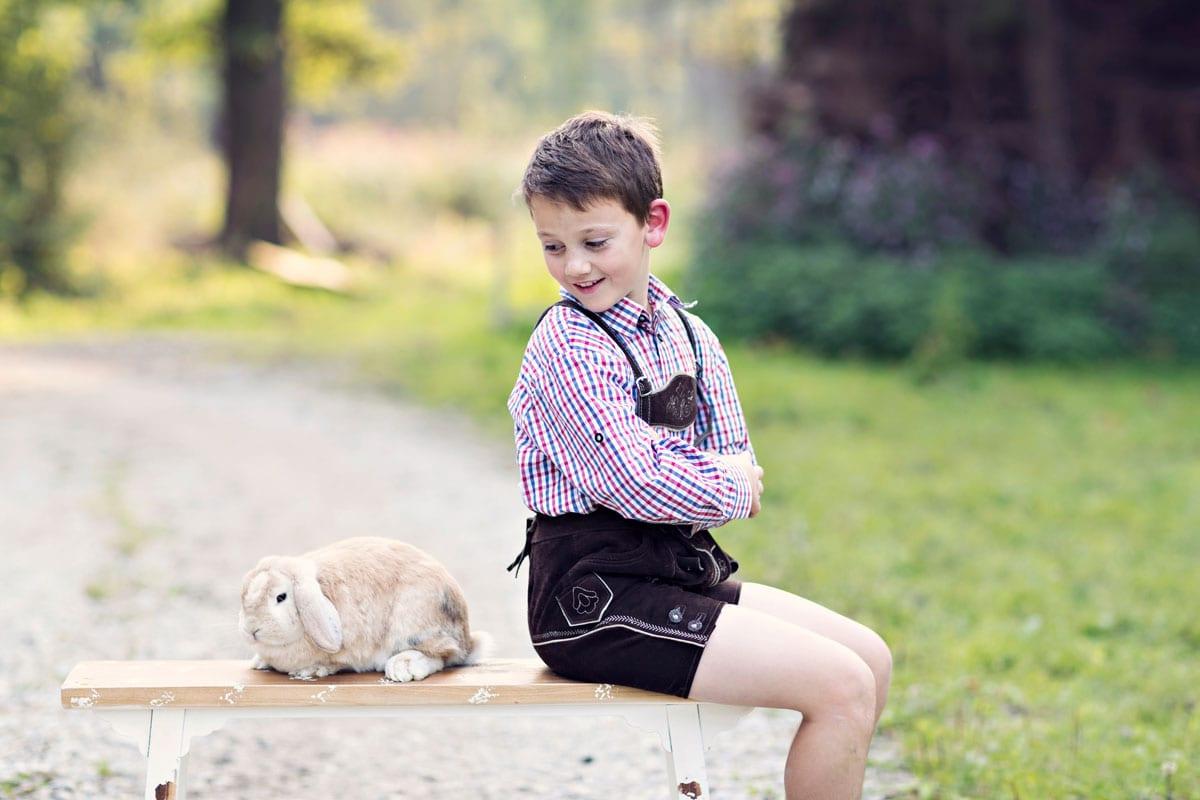 Junge sitzt auf einer Bank und betrachtet ein Kaninchen waehrend eines outdoor Fotoshootings