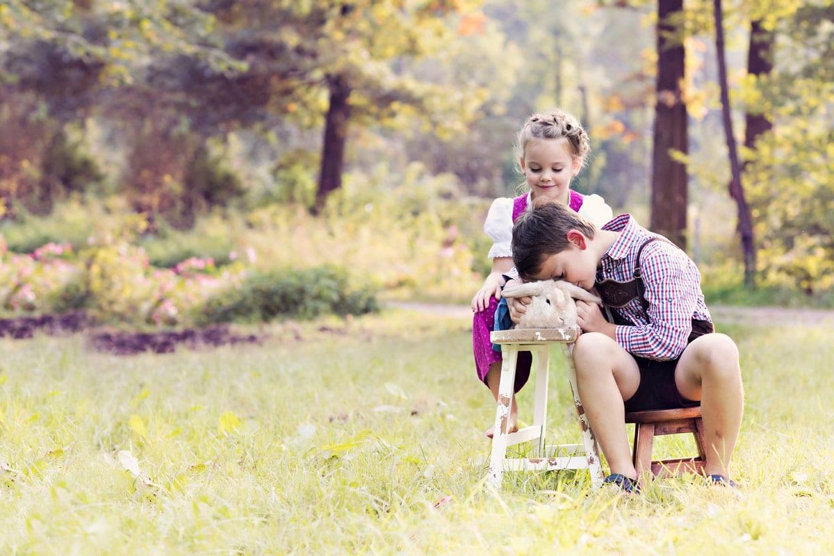 Junge und Maedchen sitzen und spielen mit einem Hasen bei einem Outdoor Fotoshooting von Carmen Bergmann