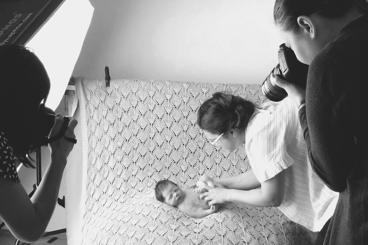 Kleines Baby schlaeft auf einem Bett waehrend es von einem Fotografen waehrend eines Workshops fuer Babyfotografie fotografiert wird