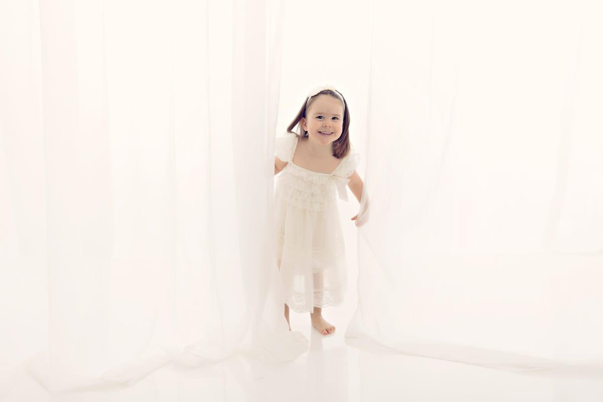 Kleines Maedchen im weissen Kleid erscheint hinter einem Vorhang in Carmen Bergman Fotostudio in Muenchen