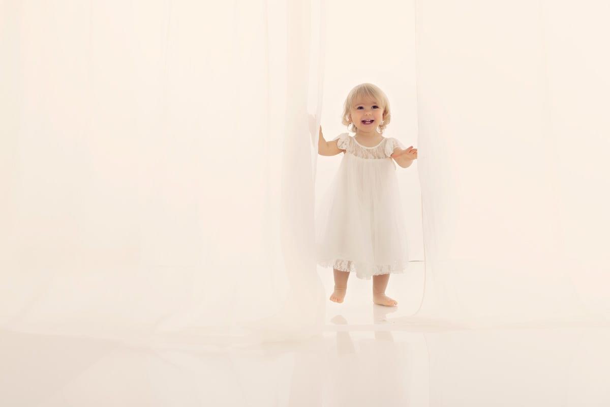 Kleines Maedchen im weissen Kleid erscheint hinter einem Vorhang und laechelt zur Kamera