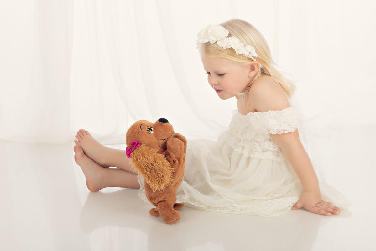 Kleines Maedchen im weissen Kleid sitzt auf Boden und spricht mit ihrem Marionettenhund waehrend eines Babyfotoshooting in Carmen Bergman in Muenchen