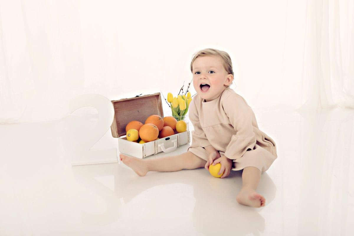 Kleines Maedchen sitzt und spielt mit Orangen in Carmen Bergman Fotostudio waehrend eines Babyfotoshootings