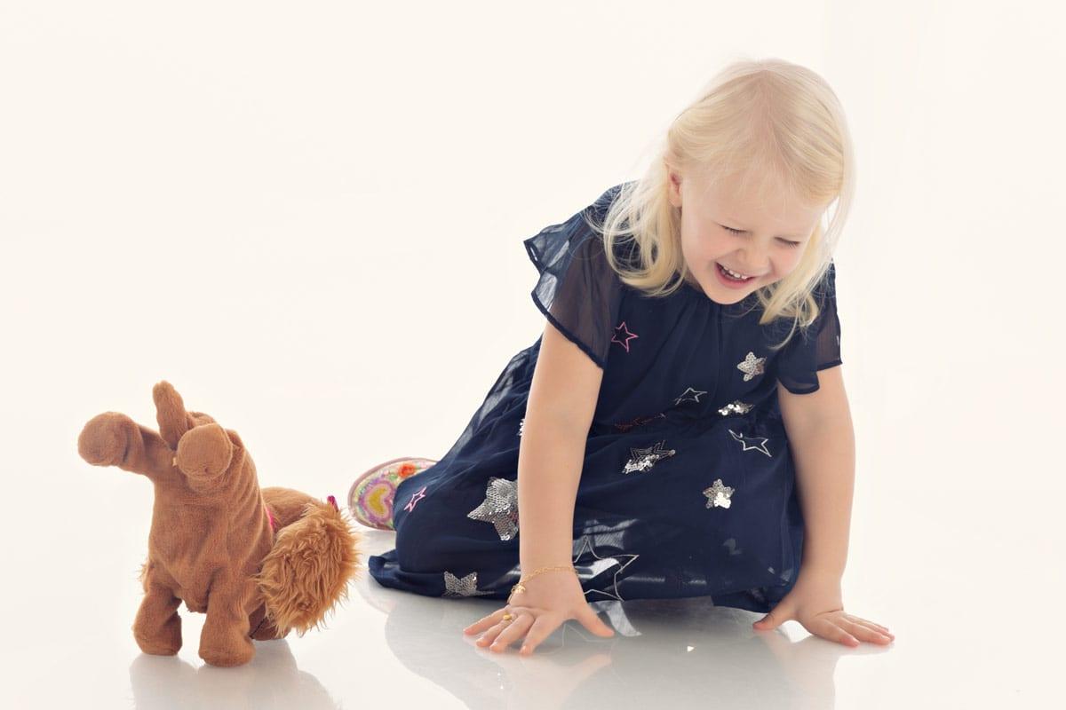 Kleines blondes Maedchen im blauen Kleid hat eine gute Zeit und lacht beim Fotoshooting im Fotostudio von Carmen Bergman