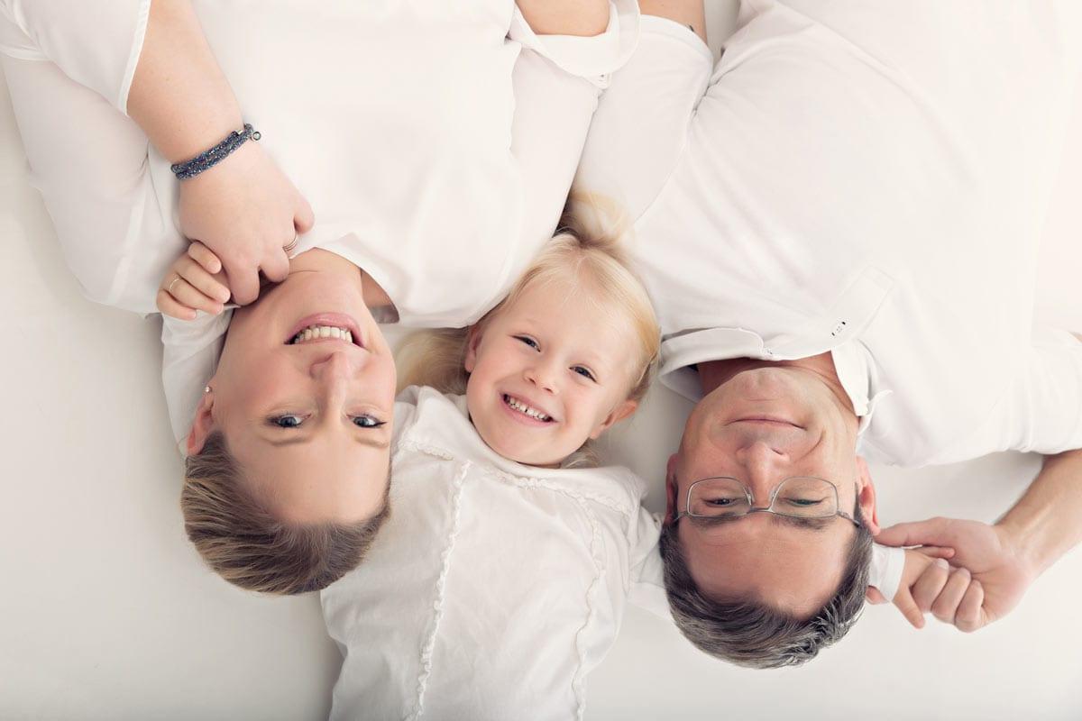 Mutter, Tochter und Vater liegen auf dem Ruecken zusammen mit den Koepfen waehrend eines Familienfotoshootings im Fotostudio von Carmen Bergmann