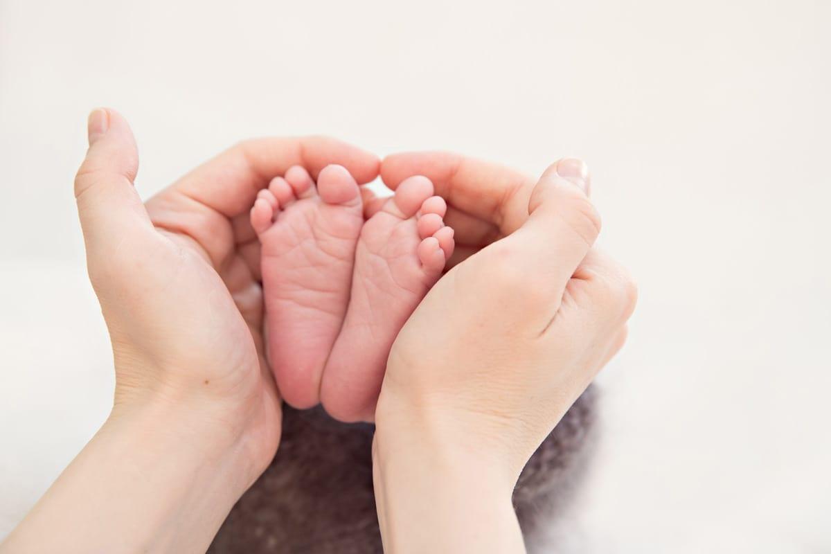 Mutter haelt die Fuesse eines neugeborenen Babys in einem Herzen mit den Haenden gemacht waehrend des neugeborenen Fotoshootings in Carmen Bergmann Photo Studio