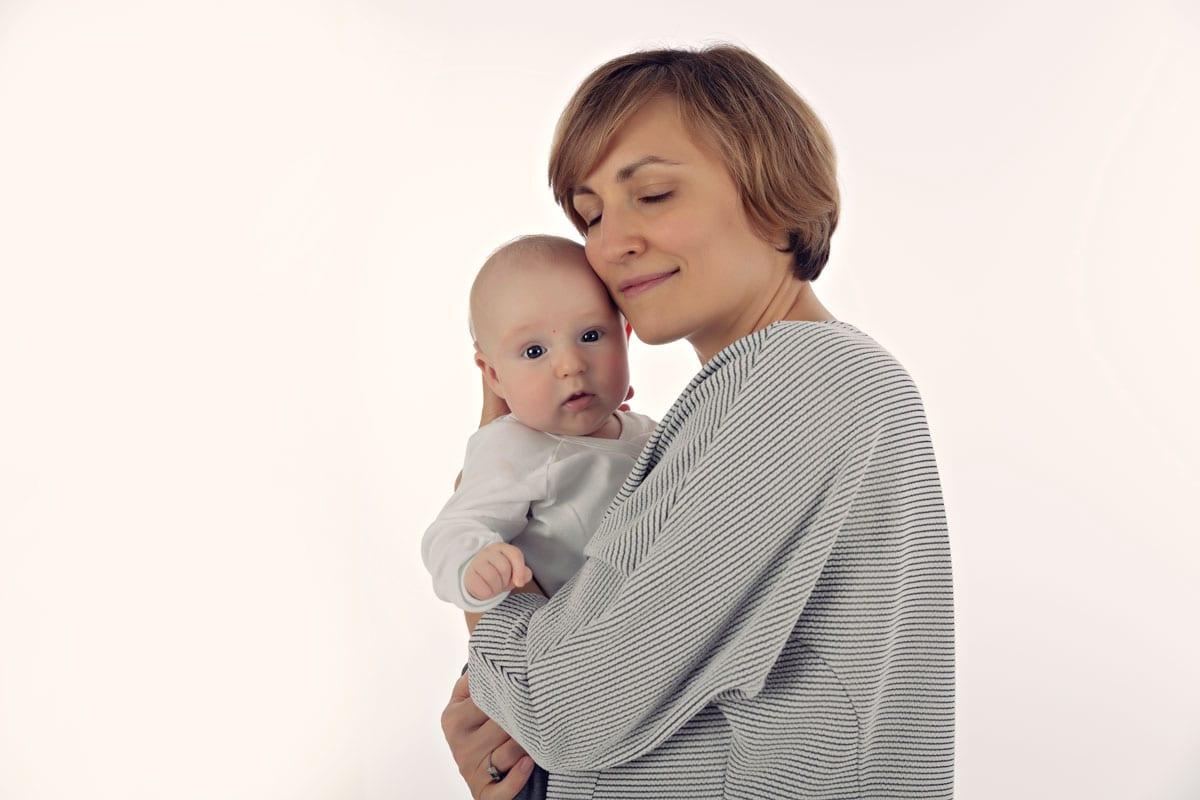 Mutter haelt ihr Baby bei einem Familienfoto im Bergmann Fotostudio in Haidhausen in den Armen