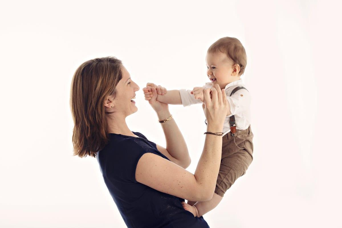Mutter haelt ihr Baby und sie laecheln zu einem anderen waehrend eines Babyfotoshootings in Carmen Bergman-Fotostudio in Muenchen