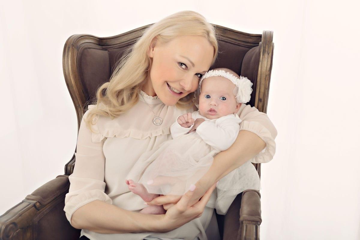 Mutter haelt ihr Baby und sitzt auf einem Lehnsessel und betrachtet die Kamera waehrend eines Babyfotoshooting in Carmen Bergman Fotostudio in Haidhausen