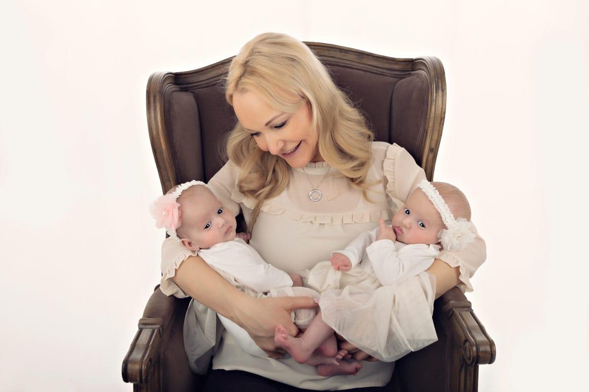 Mutter haelt ihre Maedchenzwillinge und sitzt auf einem Sessel waehrend eines Babyfotoshootings im Carmen Bergman Fotostudio