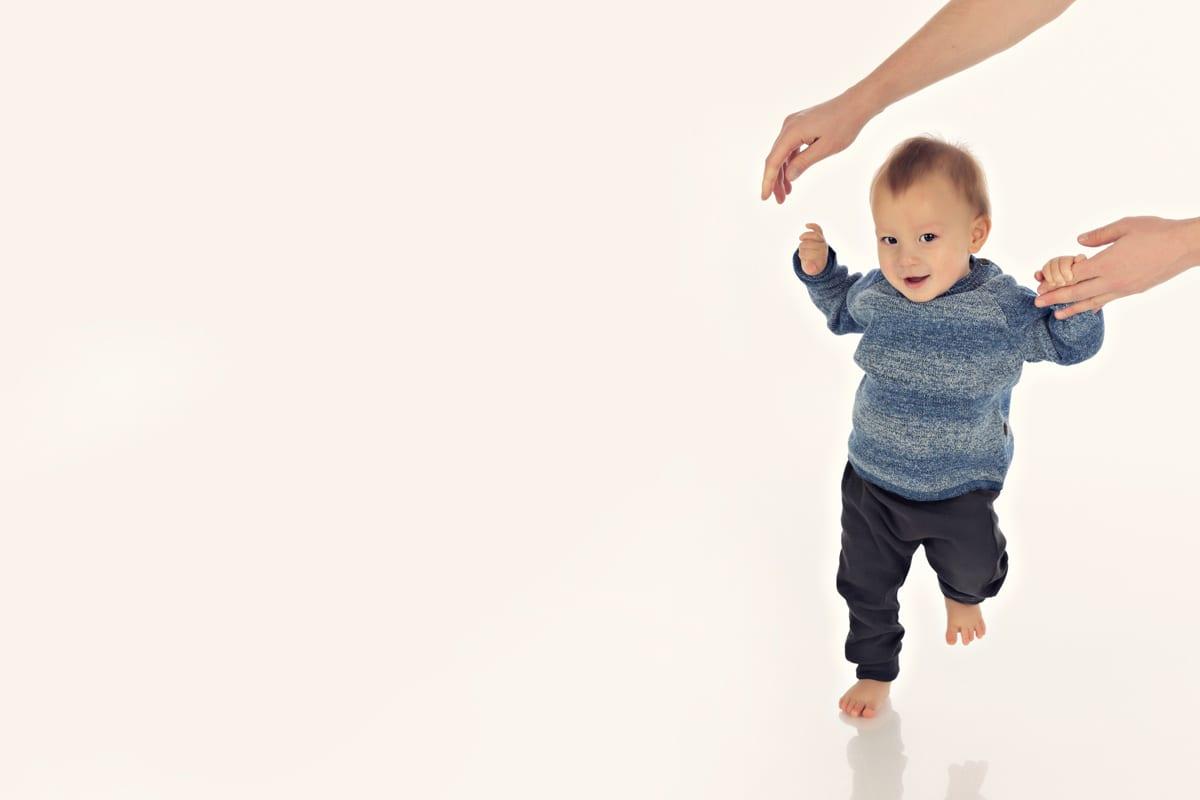 Mutter hilft Baby bei den ersten Schritten im Carmen Bergmann Studio waehrend eines Baby Fotoshootings