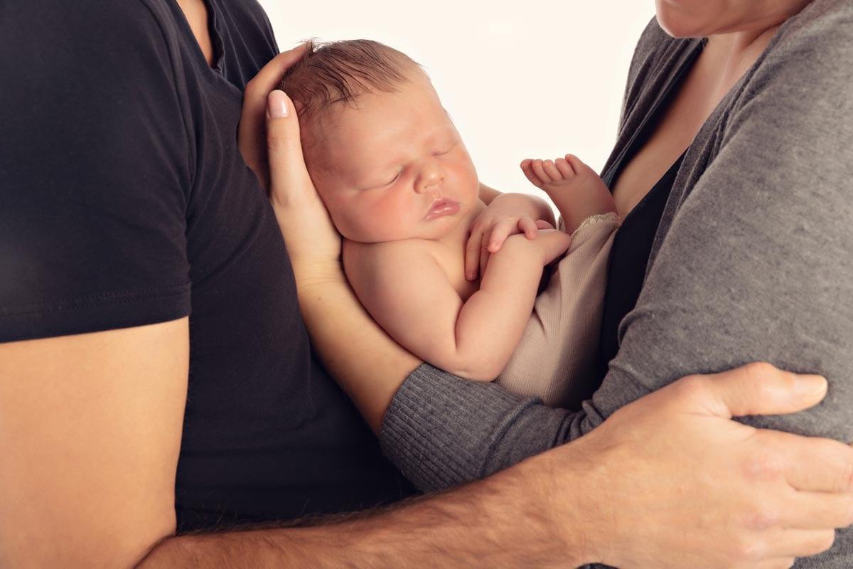 Mutter und Vater halten das Neugeborene zwischen sich beim Neugeborenen Fotoshooting im Fotostudio Carmen Bergmann in Haidhausen