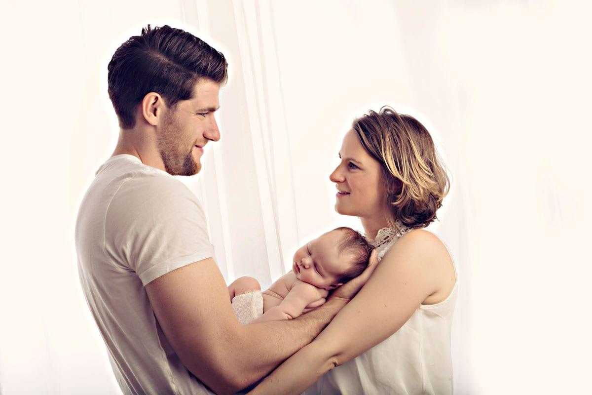 Mutter und Vater halten ihr Baby im Schlaf und sehen sich im Fotostudio Carmen Bergmann in Muenchen an