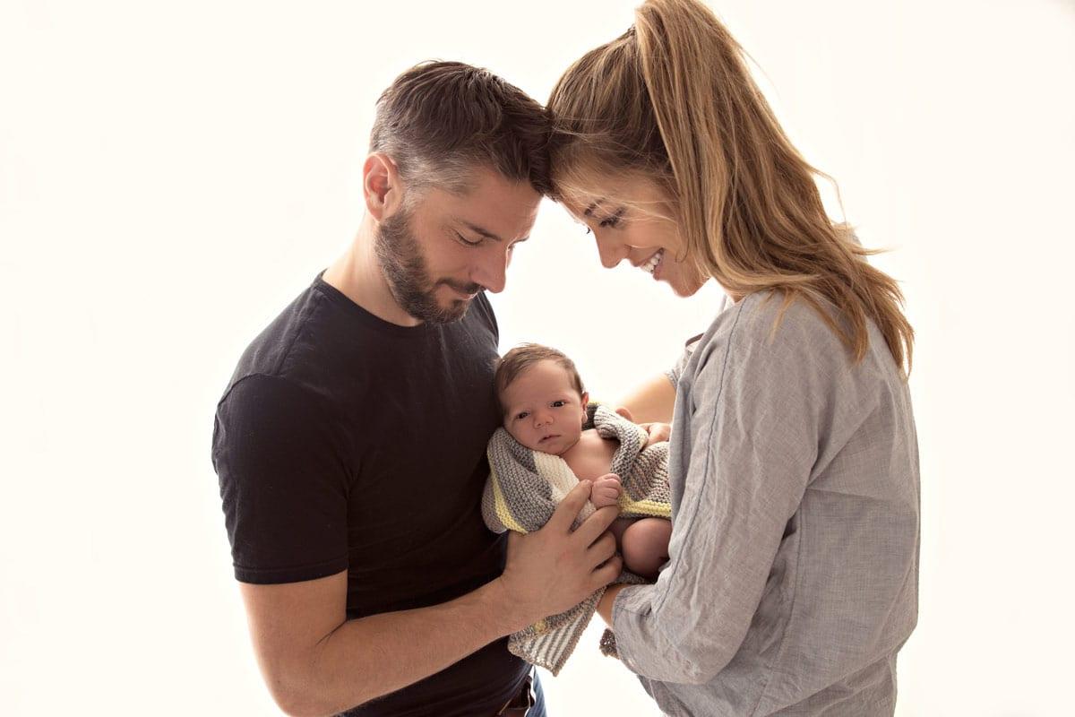 Mutter und Vater halten zusammen ein Baby bei einem Familienfoto im Carmen Bergmann Studio