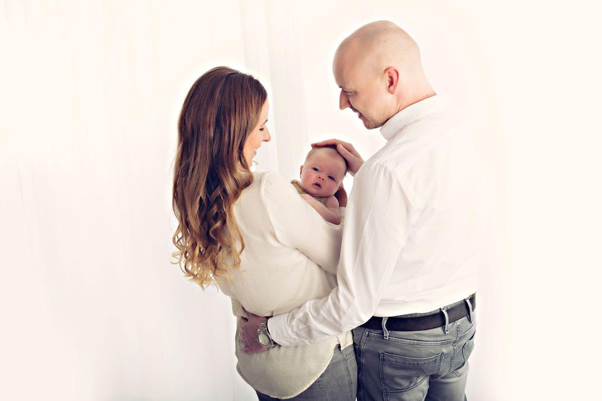 Mutter und Vater in weissen Outfits halten ihr Baby als sie waehrend eines Fotoshootings im Carmen Bergmann Studio in Muenchen in die Kamera schaut