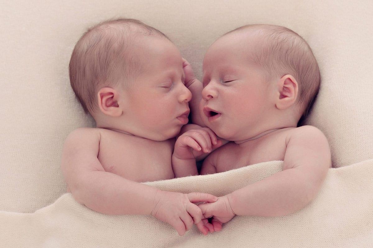 Neugeborene Zwillinge schlafen waehrend des neugeborenen Fotoshootings nebeneinander