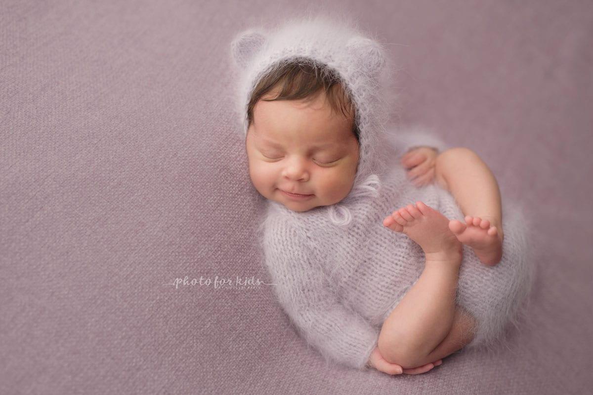 Neugeborene in weissen Outfits schlaeft auf dem Ruecken beim Neugeborenen Fotoshooting von Nicoleta Raftu