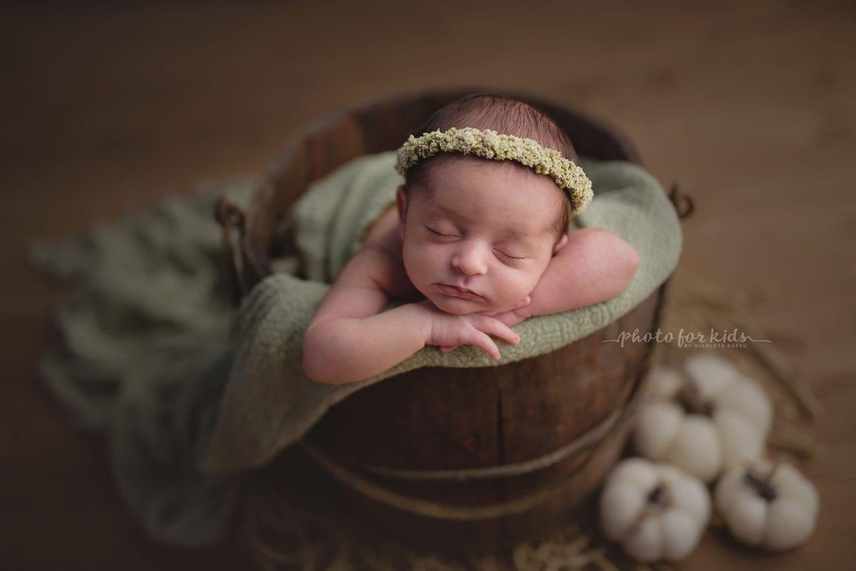 Neugeborene schlaeft in einem Eimer in einem neugeborenen Fotoshooting von Nicoleta Raftu