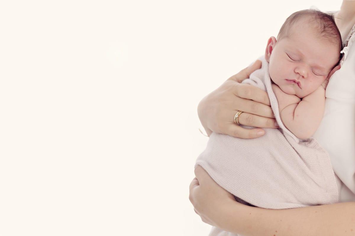 Neugeborene schlaeft waehrend des Neugeborenen-Fotoshootings in Carmen Bergmann Photo Studio in den Armen der Mutter