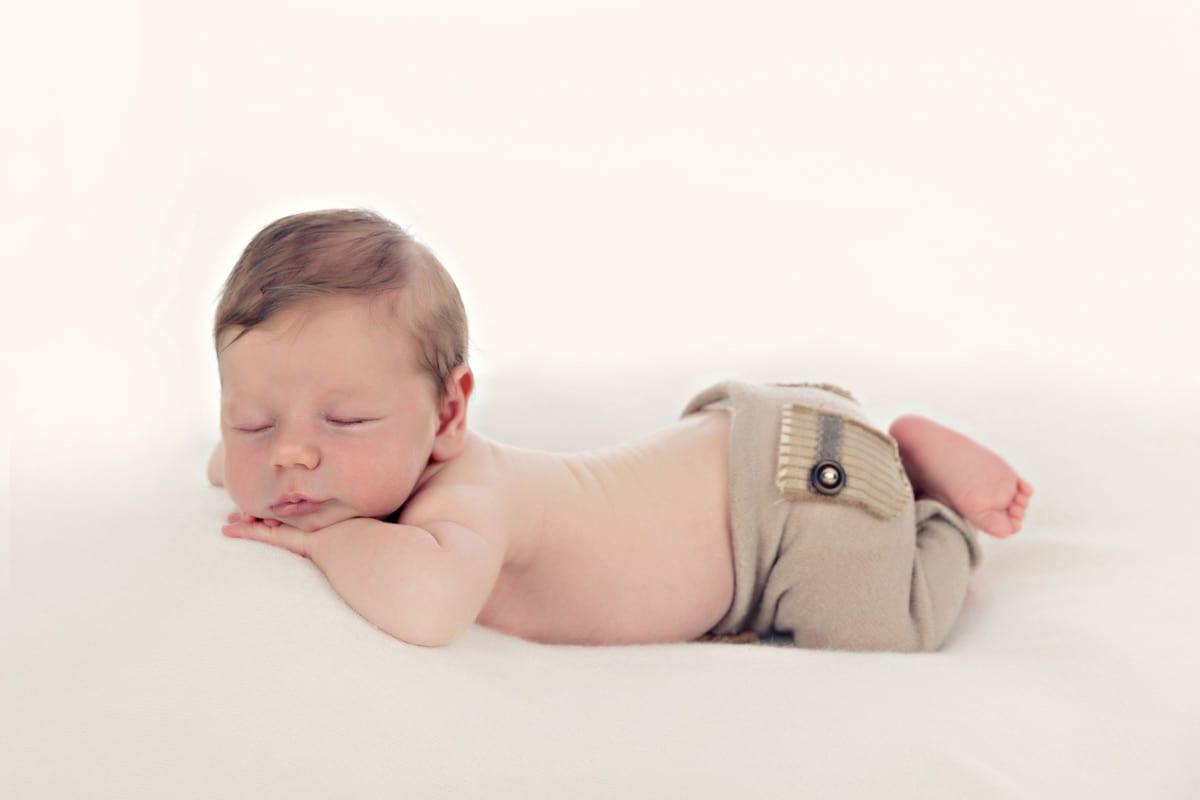 Neugeborenes Baby schlaeft auf dem Bauch in Carmen Bergmann Fotostudio in Muenchen